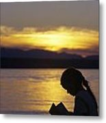 Young Girl Silhouetted Reading A Book On The Beach At Sunset Metal Print