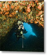 A Diver Explores A Cavern With Orange Metal Print