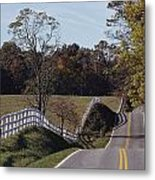 A Hilly Country Road Passes A Fenced Metal Print