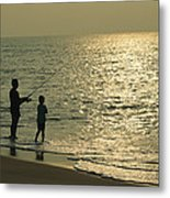 A Man And A Young Boy Fish In The Surf Metal Print