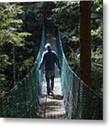 A Man Walks Across A Suspension Bridge Metal Print by Taylor S. Kennedy