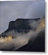 A Mountain Peaks Through The Clouds Metal Print