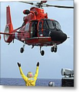 Boatswain Mate Directs A Hh-65a Dolphin Metal Print by Stocktrek Images