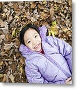Smiling Girl Lying On Autumn Leaves Metal Print