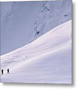 Three Hikers Walking Up A Snow Covered Metal Print