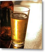 Backlit Glass Of Beer And Empty Bottle On Table Metal Print