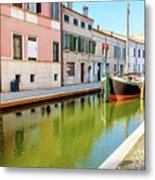 boat in a canal of the colorful italian village of Comacchio in  Metal Print