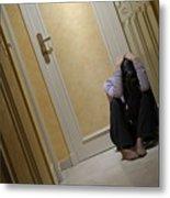 Depressed Woman Sitting In Corridor With Head In Hands Metal Print