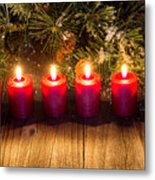 Glowing Red Candles With Snow Covered Evergreen Branch On Rustic Metal Print