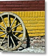Old Wooden Wheel Against A Wall Metal Print