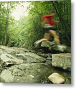 Panned View Of Man Leaping Over Rocky Metal Print by Skip Brown