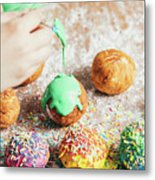 Woman's Hand Coating A Donut With Green Frosting. Metal Print