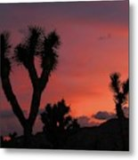 Joshua Trees Silhouetted Against A Red Sky Metal Print