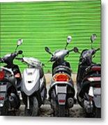 Line Of Motorbikes Against Green Metal Print
