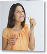 Young woman blowing soap bubbles Metal Print