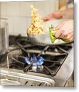 Midsection Of Chef Keeping Utensil On Stove In Kitchen Metal Print