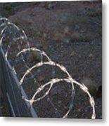Razor wire on a fence on the coast Metal Print