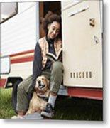 Woman with dog reading book in motor van Metal Print