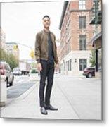 Young man standing on city sidewalk Metal Print