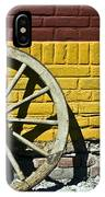 Old Wooden Wheel Against A Wall IPhone Case