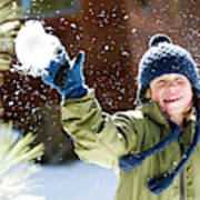 A Boy Throws A Snowball While Playing Poster