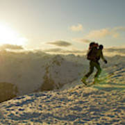 A Man Backcountry Skiing At Sunset Poster