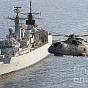 A Royal Navy Merlin Helicopter Passes Over Hms Cumberland Poster
