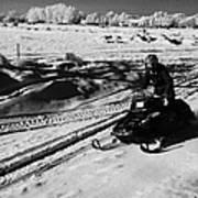man on snowmobile crossing frozen fields in rural Forget Saskatchewan Canada Poster