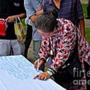 A Lady Signs Petition At May Day Rally Singapore Poster