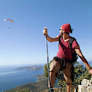 A Male Climber Looking At Paragliding Poster