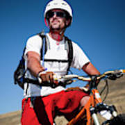 A Male Mountain Biker Stops To Enjoy Poster