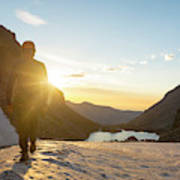 A Man Hiking On Snowfield At Sunrise Poster