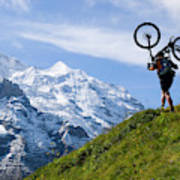 A Mountain Biker Is Carrying His Bike Poster
