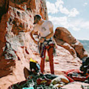 A Rock Climber Setting Up To Climb Poster
