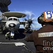 A Sailor Signals To Pilots Of An E-2c Poster