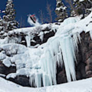 A Snowboarder Jumps Off An Ice Poster