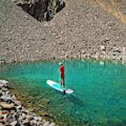 A Young Male Paddleboarding On A Small Poster