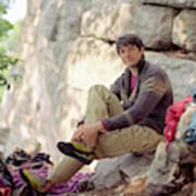 A Young Rock Climber Puts On A Climbing Poster