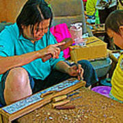 Child Watches As Mom Works In Teak Wood Carving Shop In Kanchanaburi-thailand Poster