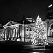 christmas tree and german flag flying fluttering on flagpole outside reichstag building Berlin Germany Poster