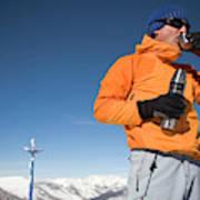 Dressed In Orange, A Skier Sips A Warm Poster