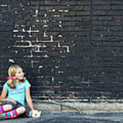 Girl Sitting On Ground Next To Brick Wall Poster