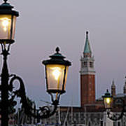 Lampposts Lit Up At Dusk With Building Poster