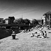 people enjoying the sunshine on the quay next to the corrib river on a sunday afternoon Galway city  Poster