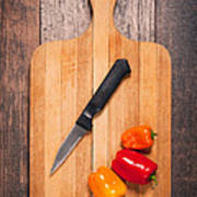 Peppers And Knife On Cutting Board Poster