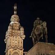 Public Statue And Skyscraper At Night Poster