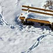 Snowy Foot Prints Around Snow Covered Park Bench Poster