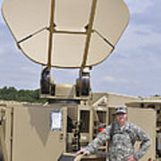 Soldier Stands Next To A Satellite Poster