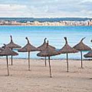 Straw Umbrellas On Empty Beach Poster