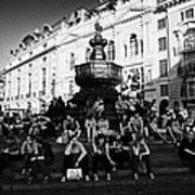 tourists and visitors sit on the steps of the eros statue in picadilly circus London England UK Poster